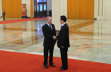 Chinese President Hu and Russian Prime Minister Putin shake hands in Beijing
