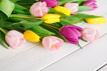 Bright tulips bouquet on white wood background, copy space