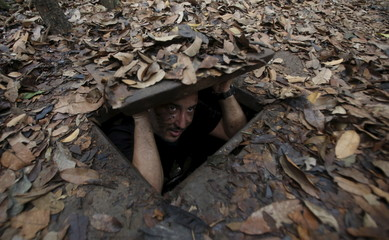 Algerian journalist Riad Abada enters the Cu Chi tunnel network through an entrance camouflaged on the jungle floor during a guided tour near Ho Chi Minh City