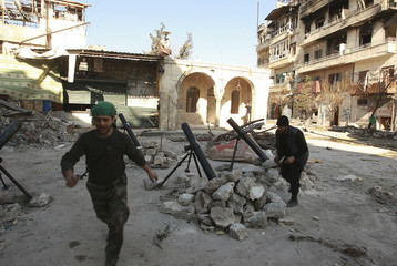 Free Syrian Army fighters react as they launch mortar shells towards forces loyal to Syria's President Bashar al-Assad in Aleppo