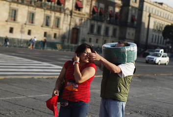 A man, with a roll of rubber vacuum hose around his head, jokes with his wife outside the National Palace in Mexico City