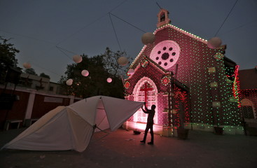 A craftsman works on a star to decorate a church ahead of Christmas in Ahmedabad