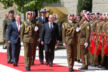 Jordan's King Abdullah and France's President Hollande review Bedouin honour guards during Hollande's visit to Jordan, at the Royal Palace in Amman