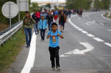 A migrant's child walks on a highway towards Vienna near Nickelsdorf