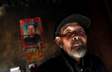 Ma Gang, 81, stands inside his house next to a portrait of former Chinese Chairman Mao Zedong in Yuangudui village, Gansu Province