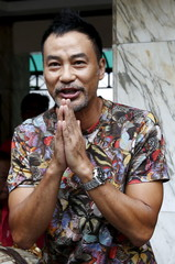 Hong Kong actor Simon Yam gestures during his visit to the Erawan shrine in central Bangkok
