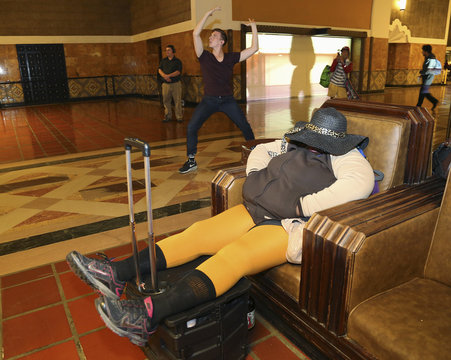 """Performers from L.A. Dance Project dance near person resting in chair during dress rehearsal for the experimental opera """"Invisible Cities"""", which is presented inside historic Los Angeles Union Station in California"""