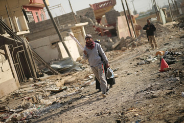 Displaced Iraqis leave their house in the frontline neighbourhood of Intisar, eastern Mosul