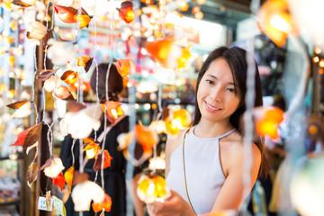 Woman choosing the decoration lamp in street market