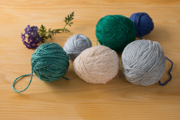 Colorful yarns for knitting and flower on a wooden bakground.