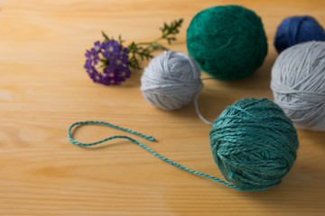 Colorful yarns for knitting on a wooden table.