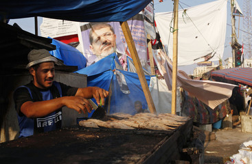 A supporter of deposed Egyptian President Mursi grills fish for protesters in the sit-in area of Rab'a al- Adawiya Square