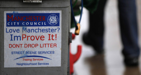A pedestrian walks past a council rubbish cart in Manchester
