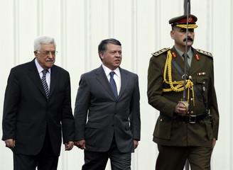 Palestinian President Abbas walks with King Abdullah of Jordan during a welcoming ceremony in Ramallah