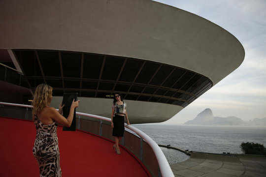 A woman poses for a photo at the Contemporary Art Museum (MAC) as the Sugar Loaf mountain is seen in the background at the Niteroi city in Rio de Janeiro state