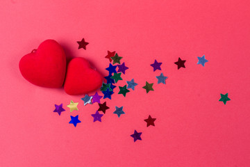 St Valentines day. Two red hearts and a lot of color of stars on a red background.