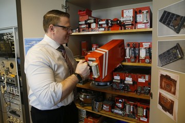 An employee of Germany's Bundesamt fuer Fluguntersuchung BFU removes a flight recorder from a cupboard at their headquarters in Braunschweig