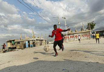 Men play soccer on the hillside in Port-au-Prince