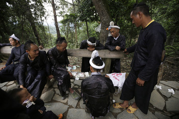 Ethnic Miao man Gun Yuangu and other villagers wait  to share the money they earned from performance in Congjiang county
