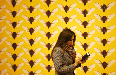 A woman walks past a stand advertising printed wallpaper at the 100% Design exhibition at Earl's Court in London