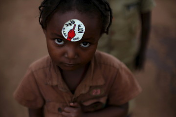 """A girl with a sticker on her forehead reading """"Allah is one""""  looks on in a compound sheltering internally displaced Muslims at the central mosque in the PK 5 neighbourhood of Bangui"""