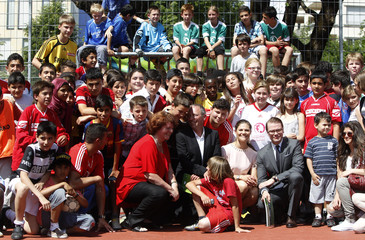 Sweden's Crown Princess Victoria and husband Prince Daniel pose with youth club members in Munich