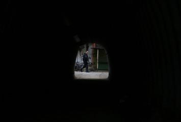 A police officer patrols the Parque Alegria slum during an operation in Rio de Janeiro