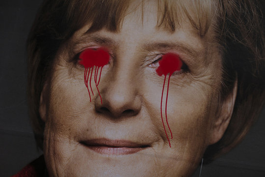 Paint is splashed onto an election campaign poster of German Chancellor and CDU leader Merkel in Berlin
