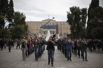 Members of the Greek Army's music band perform during a rehearsal on main Syntagma square in Athens as the parliament is pictured in the background