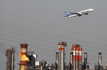 An All Nippon Airways' plane flies over a chimney of an oil refinery in Kawasaki