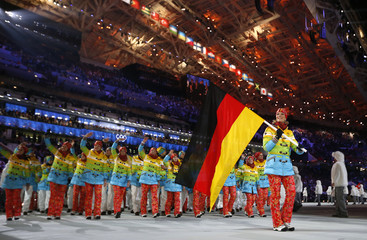 Germany's flag-bearer Maria Hoefl-Riesch leads her country's contingent as they march in during the opening ceremony of the 2014 Sochi Winter Olympics