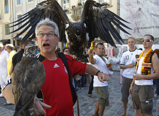 A Denmark soccer fan poses for picture with eagles as Germany fans watch in central Lviv