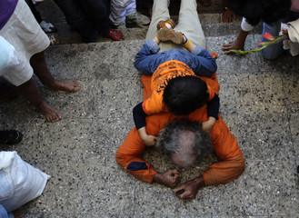 A man crawls, for several kilometres, with his son on his back as an offering at the entrance of the shrine of Saint Lazarus in the town of Rincon