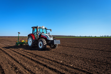 Fototapete - Agriculture tractor sowing seeds and cultivating field. Blue sky!
