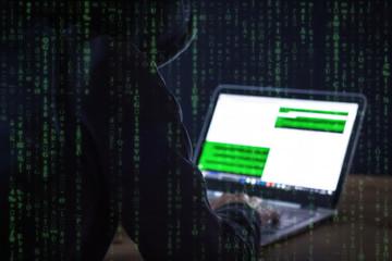 Mann mit Kapuzenpullover beim Hacken.