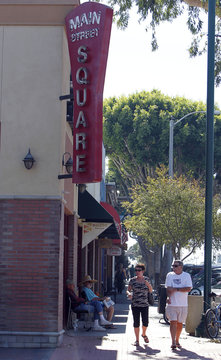 People walk along downtown area looking south on Main Street in Seal Beach