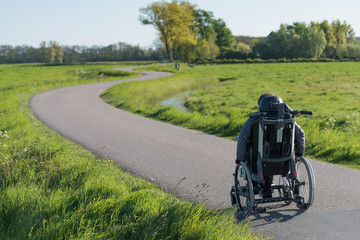 A disabled person in a wheelchair going along a long and winding road