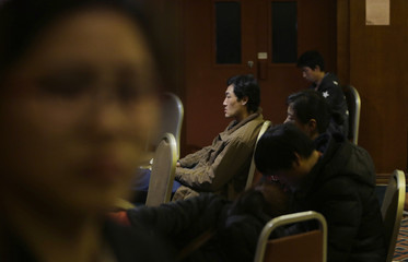 Family members of passengers aboard the missing Malaysia Airlines flight MH370 wait for news from Malaysia Airlines at a hotel in Beijing