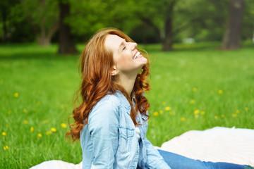 frau sitzt draußen im grünen und lacht
