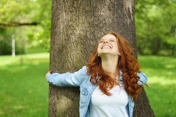 glückliche frau lehnt sich lachend an einen baum und schaut nach oben