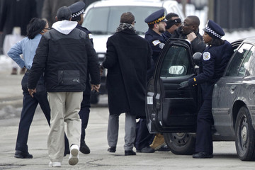 Police take a man into custody after a fight broke out in Chicago, as mourners line up before the funeral of Hadiya Pendleton, who was fatally shot in what police say was a case of mistaken identity in a gang turf war
