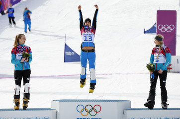 Austria's first-placed Dujmovits jumps onto the podium as Germany's Karstens and Germany's Kober look on during the flower ceremony for the women's parallel slalom snowboard event at the 2014 Sochi Winter Olympic Games in Rosa Khutor