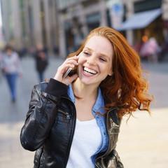 lachende frau ist unterwegs und telefoniert mit ihrem smartphone