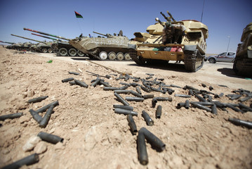 A rebel fighter checks a tank, captured from forces loyal to Libyan leader Muammar Gaddafi in the rebel-held town of Zintan
