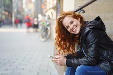 lachende frau sitzt auf einer treppe in der stadt mit ihrem handy