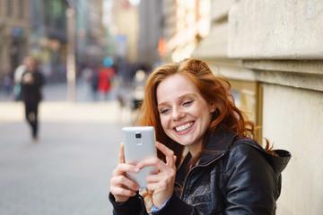 lachende frau macht ein foto mit ihrem handy