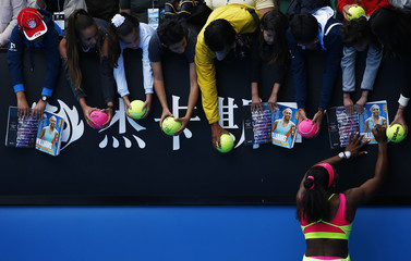 Williams of the U.S. signs autographs after defeating Muguruza of Spain during their women's singles fourth round match at the Australian Open 2015 tennis tournament in Melbourne