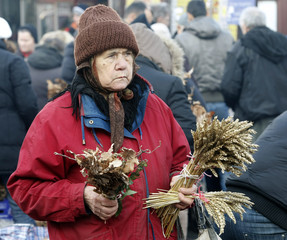 A woman sells dried oak leaf branches and sheaves of dried wheat, symbols of the traditional Yule log, in Belgrade
