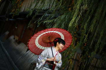 A woman, dressed in a traditional Japanese kimono, poses for tourists in Kyoto