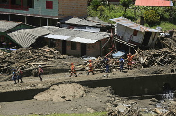 Rescue workers walk past houses that were destroyed after a landslide sent mud and water crashing onto homes close to the municipality of Salgar